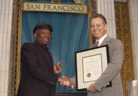 Aus gegebenen Anlass präsentierte der Bürgermeister von San Francisco, Willie Brown (links), der Kirche eine Proklamation, in der er sie für ihre Bemühungen lobte, das Bay-Gebiet für Menschen jeder Rasse, Farbe, jedes Glaubens und aller Lebensbereiche zu einem besseren Ort zu machen.